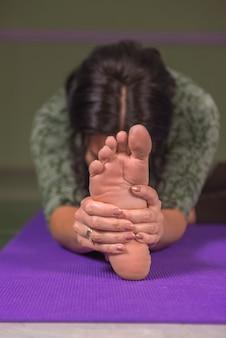 Yogi vrouw rekt yoga houdingen in fitness klasse.