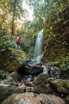 Yojoa-meer, honduras: een jongen met zijn armen omhoog in de waterval van het cerro azul meambar national park (panacam)