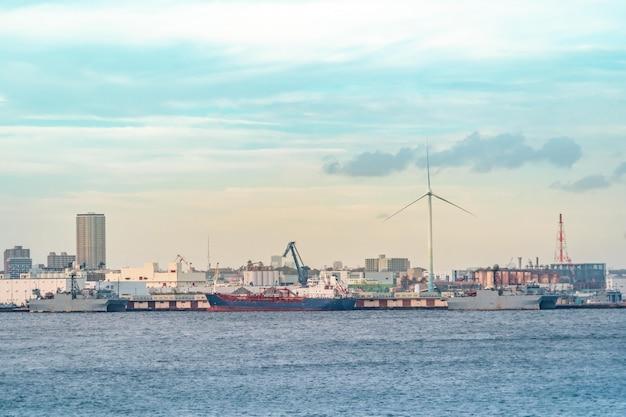 Yokohama industrial port met transportschip en windmolen.