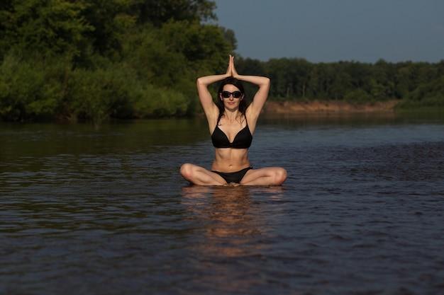 Yong europese vrouw in bikini yoga maken in de rivier