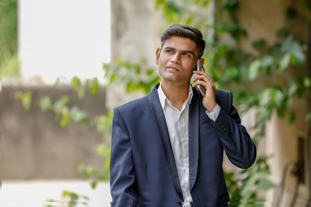 Yong indiase zakenman met behulp van smartphone