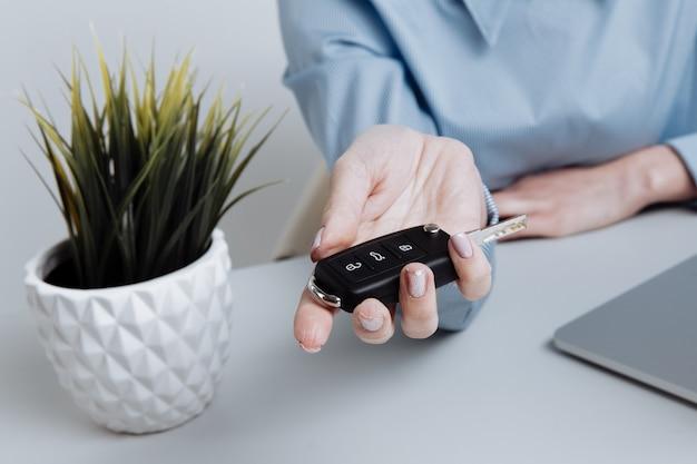 Yong mooie vrouw die sleutels vasthoudt en aan de klant geeft. contract voor het kopen van een auto.