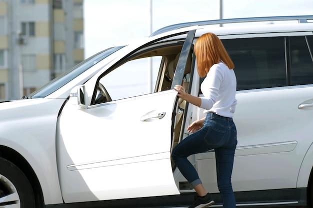 Yong mooie vrouw die zich in de buurt van een grote terreinwagen buitenshuis. bestuurdersmeisje in vrijetijdskleding buiten haar voertuig.