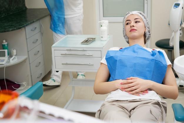 Yong mooie vrouw zittend in tandheelkundige stoel in het kantoor van de tandarts, vrouw patiënt bij de tandarts te wachten om te worden gecontroleerd