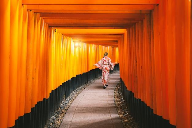 Yongvrouwen in traditionele japanse kimono's die bij het heiligdom van fushimi inari lopen