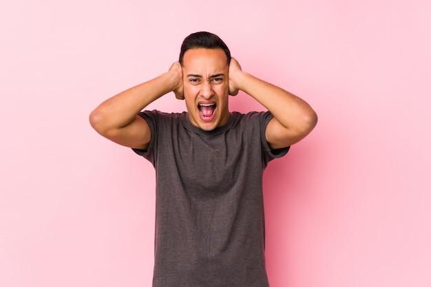 Yooung latijns-man poseren in een roze backgroundcovering oren met handen proberen niet te hard geluid te horen.