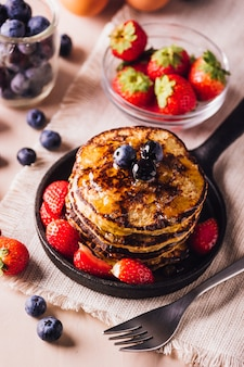 Yop zicht op stapel zelfgemaakte pannenkoeken met bosbessen en aardbeien, perfect voor het ontbijt