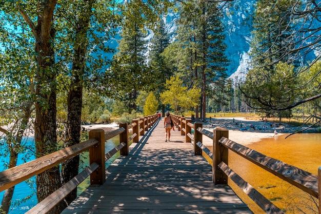 Yosemite national park, californië, verenigde staten. een jong meisje op de swinging bridge, yosemite valley. verticale foto