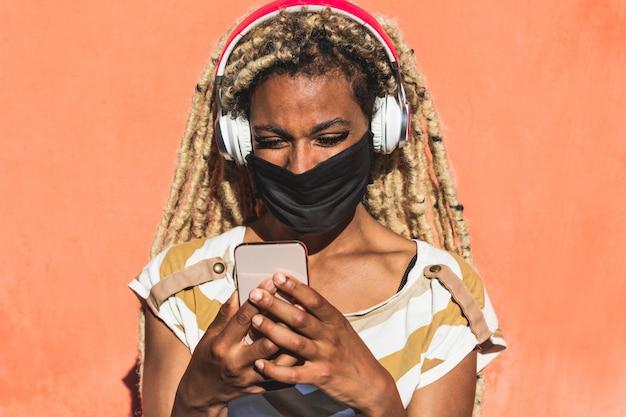 Yound afrikaanse vrouw met blonde dreadlocks die mobiele telefoon met behulp van terwijl het luisteren van afspeellijstmuziek