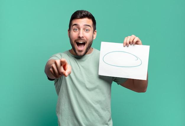 Younf knappe man met een vel papier met een kopieerruimte