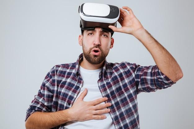 Young bang bebaarde man in shirt met virtual reality-apparaat