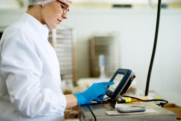 Young gericht vrouwelijke werknemer in steriele doeken met behulp van een complexe machines in de fabriek productielijn.