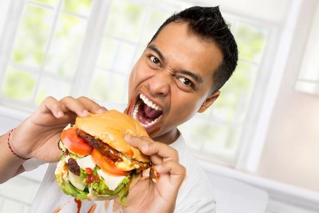 Young man heeft een groot verlangen om een hamburger te eten