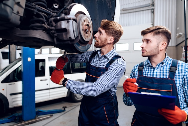 Young mechanics repairs automotive hub in garage.
