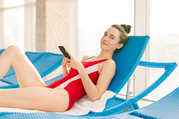 Young passen brunette vrouw in zwembroek scrollen in smartphone terwijl u ontspant na het zwemmen
