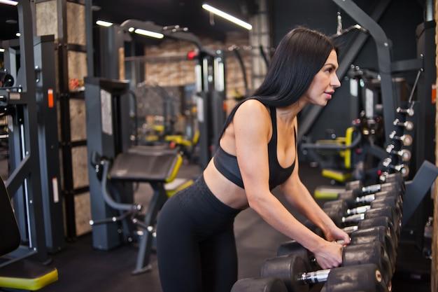 Young passen vrouw die een halter uit het rek in de sportschool