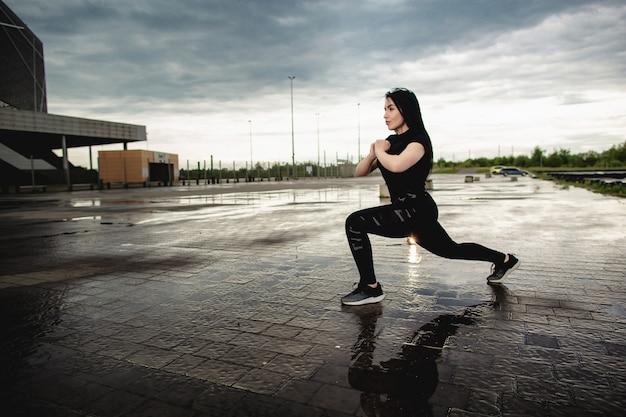 Young passen vrouw in sportkleding doen lunges. de vrouw leidt in openlucht na regen op. fitness, training, sport buitenshuis concept.