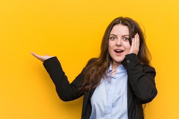 Young plus size blanke zakenvrouw houdt kopie ruimte op een palm, houden hand over wang. verbaasd en blij.