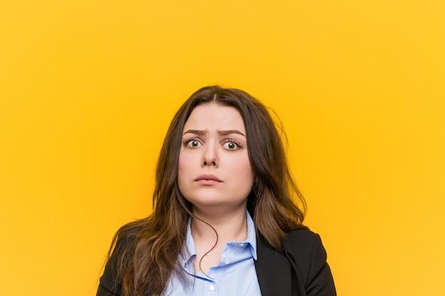 Young plus size kaukasische zakenvrouw haalt schouders op en open ogen verward.