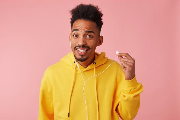Young vroeg zich af afro-amerikaanse man in gele hoodie, hoorde de vraag niet, hield zijn koptelefoon vast, keek met wijd open ogen en mond, staat.