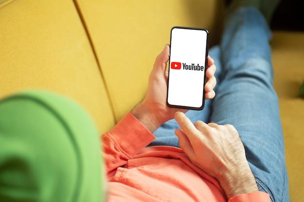 Youtube-applicatie in een smartphonescherm in de hand. internetbedrijf en videodienst youtube-concept.