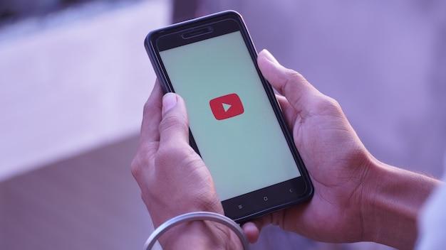 Youtube splash screen logo in mobiel en mobiel in de hand