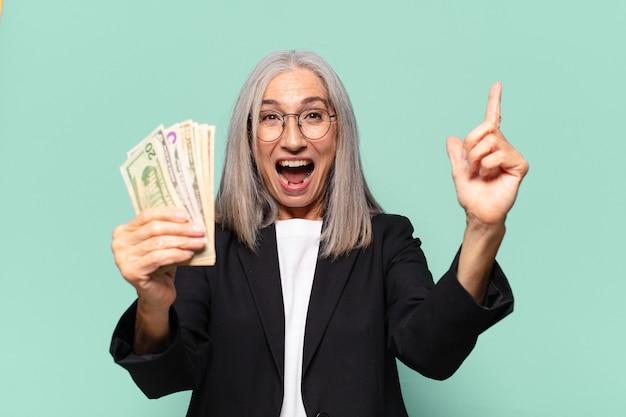 Ysenior mooie onderneemster met dollarbankbiljetten. geld concept