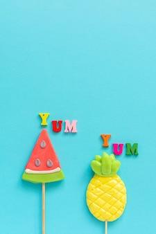 Yum yum, ananas en watermeloenlollipopson blauwe gele achtergrond. concept vakantie of vakantie