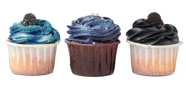 Yummy drie cupcakes met suikerglazuur op wit wordt geïsoleerd dat