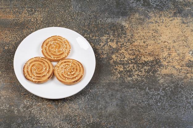 Yummy koekjes van sesamzaden op witte plaat.