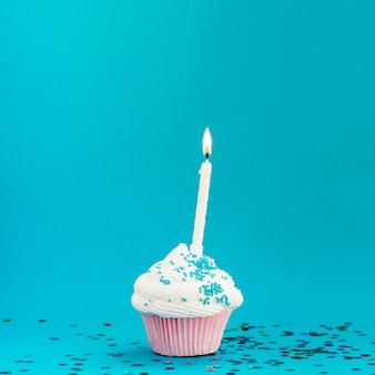 Yummy verjaardagsmuffin op blauwe achtergrond