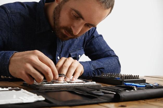 Yung bebaarde meester kijkt in een gedemonteerd elektronisch apparaat terwijl hij het met gereedschap repareert