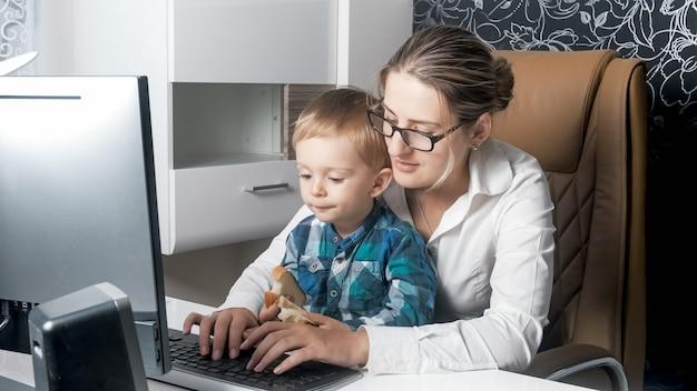 Yung zakenvrouw zit met kind thuis en werkt op de computer vanuit kantoor aan huis.