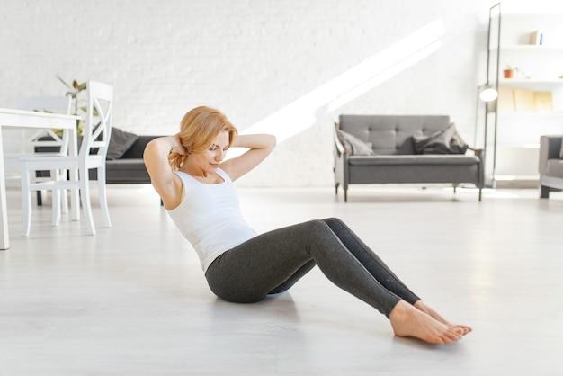 Yuong vrouw doet ochtendoefening op de vloer in de woonkamer met interieur in witte tinten.