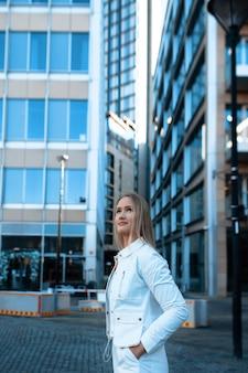 Yuong-vrouw in wit kostuum die door stad loopt