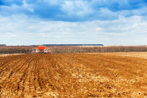 Zaaien van granen lente oude tractor die tarwe oplevert in de lente