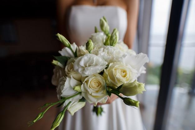 Zacht bruidboeket van witte bloemen. teder huwelijksboeket van anjers dicht omhoog. boeket witte bloemen in handen van een jonge vrouw. mooie en stijlvolle bloemsamenstelling op.