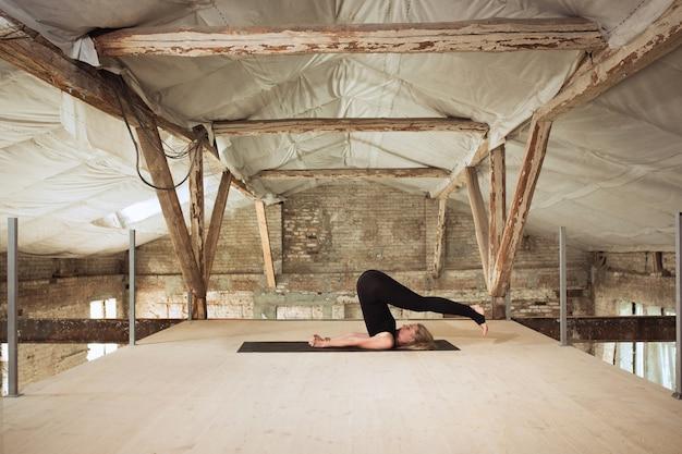 Zacht. een jonge atletische vrouw oefent yoga op een verlaten bouwgebouw. geestelijke en lichamelijke gezondheid. concept van een gezonde levensstijl, sport, activiteit, gewichtsverlies, concentratie.