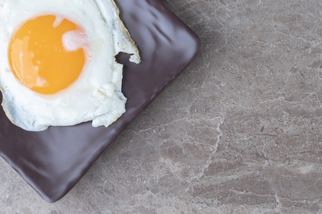 Zacht gebakken ei op donkere plaat.