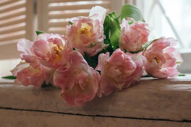 Zacht gefocust boeket van roze bloemen liggend op de vensterbank houten jaloezie op de achtergrond