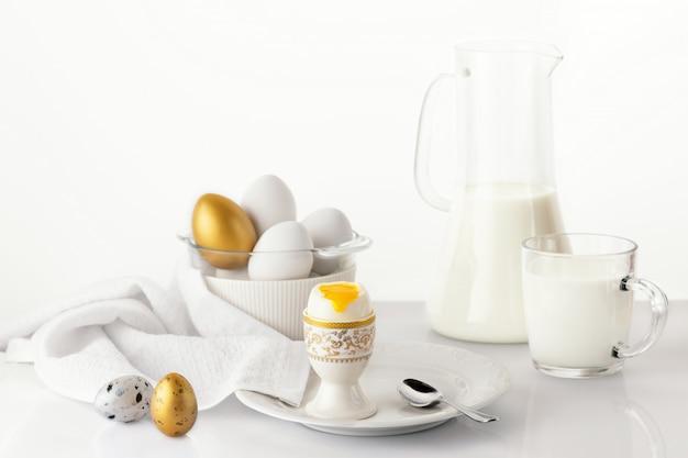 Zacht gekookt ei op een witte plaat met gouden en witte paaseieren, kwarteleitjes en melk. pasen ontbijt concept.