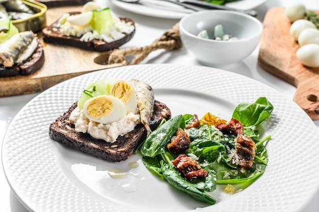Zacht gekookte eieren en ingeblikte sardines sandwiches met salade met spinazie en gedroogde tomaten op witte plaat