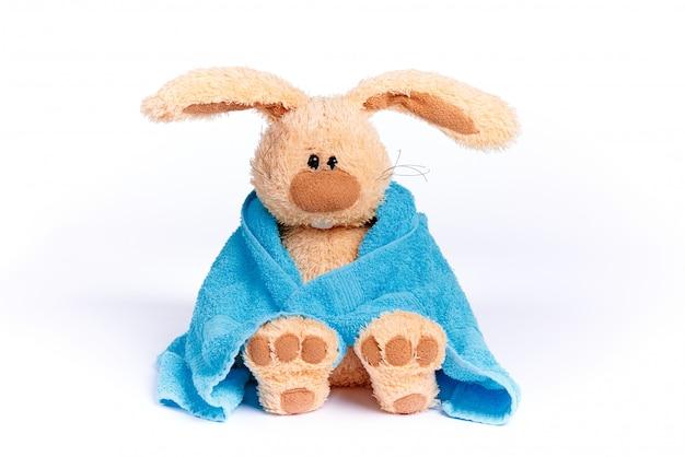 Zacht gevuld konijntje in een blauwe handdoek op een witte achtergrond.