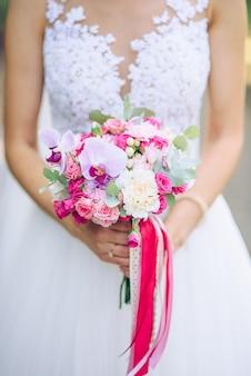 Zacht huwelijksboeket van wit en roze daalt in handen van de bruid