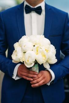 Zacht huwelijksboeket van witte pioenen in de handen van de bruidegom