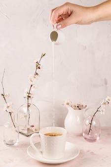 Zacht licht minimalistisch stilleven met een motie van room die in koffie gieten