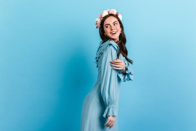Zacht meisje met sneeuwwitte glimlach kijkt rond. model met kroon van bloemen en zijden jurk poseren op blauwe muur.