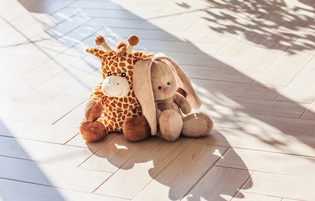 Zacht pluchen speelgoed giraf en konijn voor kinderen zitten op houten achtergrond, hard licht en schaduw