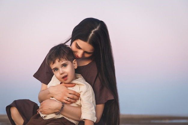 Zacht portret van een jonge moeder met haar zoontje. gouden uur geschoten bij zonsondergang buitenshuis.