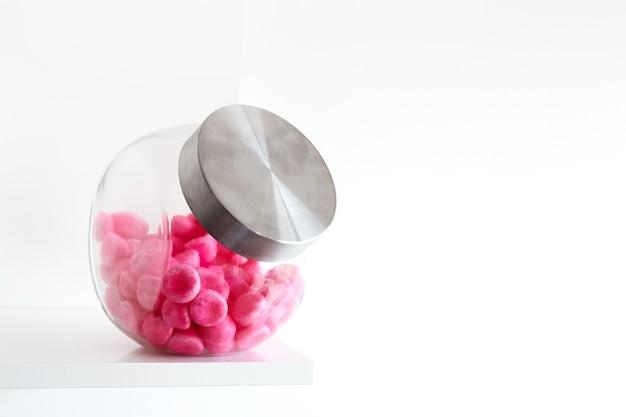Zacht roze snoep in een glazen pot op een witte plank